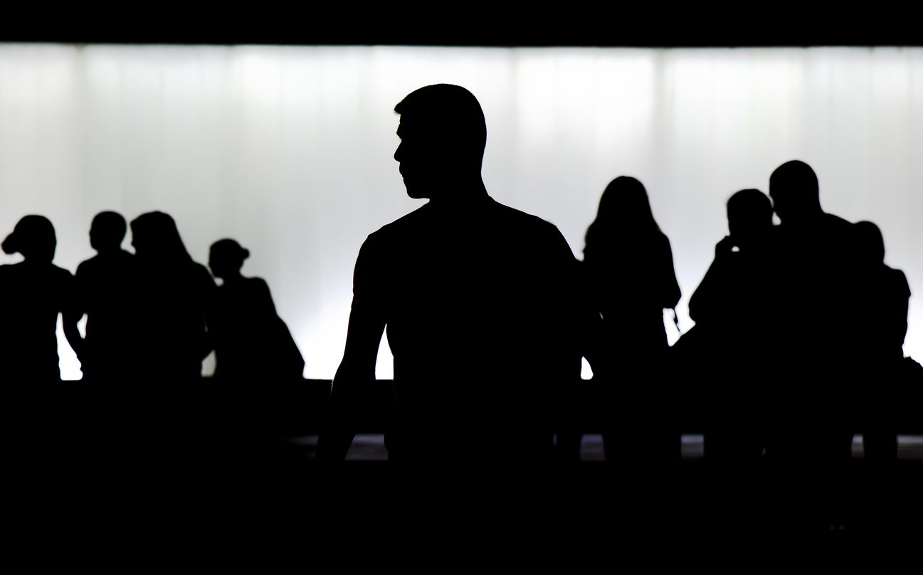 Belgrade, Serbia - June 3, 2018: Silhouette of young man standing alone in front of the crowd of young people walking blurred behind him in front of the building in the night